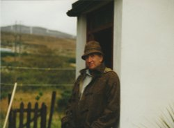 Hamilton sloan The Artist sporting a donegal tweed coat and hat outside the front door of Cottage Coshclady between Gweedore and Bunbeg county Donegal