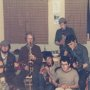 a group of us having a musical jam session in the fish factory hostel on the Vestmann island off the south coast of iceland in nineteen sixty five the instruments being played are two guitars bongo drums tin whistle saxophone and myself sporting donegal tweed hat and clarinet