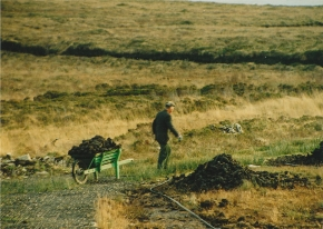 Donegal man carting turf in a wheelbarrow