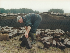 Donegal man footing sods of turf to dry
